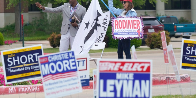 R.C. Maxwell, left, and Leah Kortre wave to voters arriving to cast their ballot during early voting Tuesday, April 27, 2021, in Mansfield, Texas. (AP Photo/LM Otero)