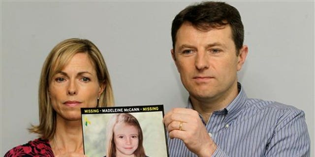 In this May 2, 2012 file photo, Kate and Gerry McCann pose for the media with a missing poster depicting an age progression computer-generated image of their daughter Madeleine at nine years of age, to mark her birthday and the 5th anniversary of her disappearance during a family vacation in southern Portugal in May 2007. (AP Photo/Sang Tan, File)