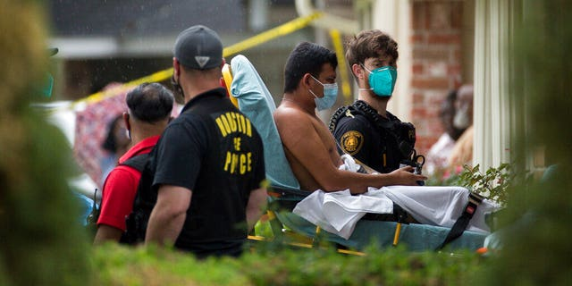 Paramedics transport a man into an ambulance from the scene of a human smuggling case, where more than 90 undocumented immigrants were found inside a home on the 12200 block of Chessington Drive, Friday, April 30, 2021, in Houston.