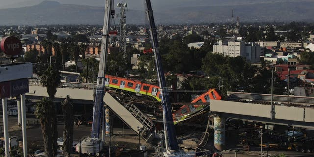 Subway cars dangle at an angle from a collapsed elevated section of the metro, in Mexico City, Tuesday, May 4, 2021. (AP Photo/Fernando Llano)