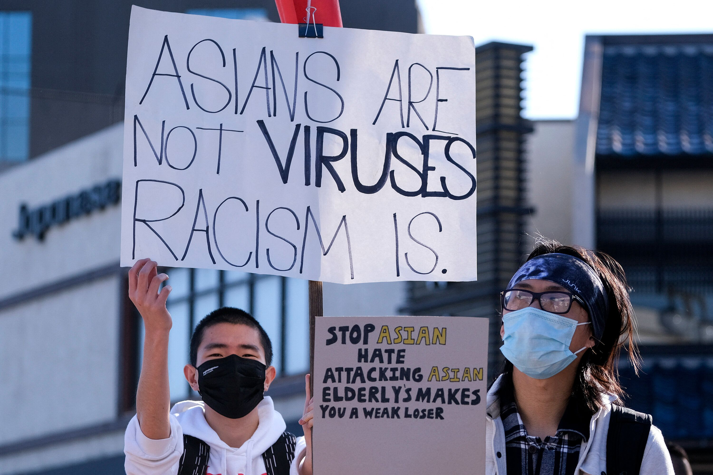 """Demonstrators wearing face masks and holding signs take part in the rally """"Love Our Communities: Build Collective Power"""" to r"""