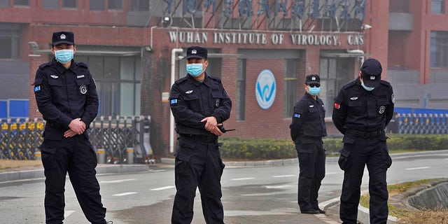 Security personnel gather near the entrance of the Wuhan Institute of Virology during a visit by the World Health Organization team in Wuhan in China's Hubei province on Wednesday, Feb. 3, 2021. (AP Photo/Ng Han Guan)