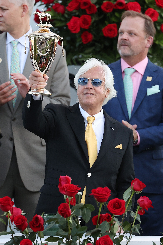 Trainer Bob Baffert raises the trophy after winning the 147th running of the Kentucky Derby with Medina Spirit, his seventh c
