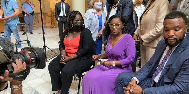 Relatives of Ahmaud Arbery, including sister Jasmine Arbery, left, and mother, Wanda Cooper Jones, second from left, sit at the Georgia state capitol in Atlanta on Monday, May 10, 2021. They witnessed Georgia Gov. Brian Kemp sign a law repealing citizen's arrest in Georgia, partly blamed for Ahmaud Arbery's fatal shooting death near Brunswick in 2020. (AP Photo/Jeff Amy)