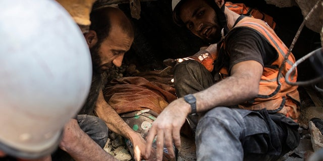 Palestinian rescuers pull the body of a woman from under the rubble of a destroyed residential building following deadly Israeli airstrikes on Gaza City that flattened three buildings and killed at least 26 people, in Gaza City, Sunday, May 16, 2021. (AP Photo/Khalil Hamra)