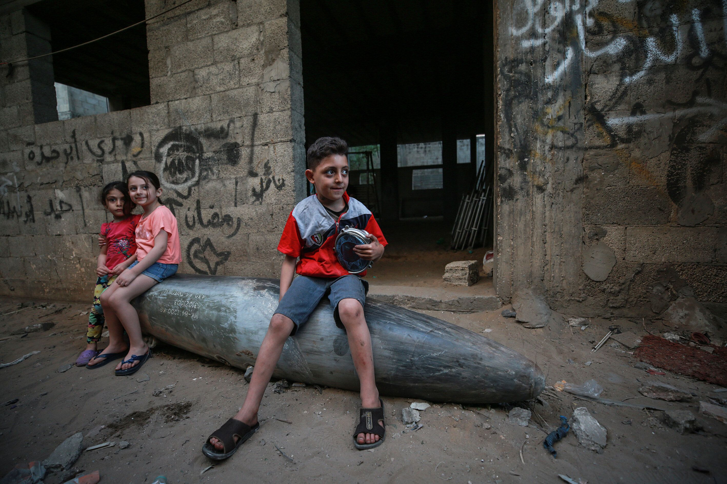 Palestinian children sit on an unexploded missile from an Israeli warplane Tuesday in the al-Rimal neighborhood of Gaza City,