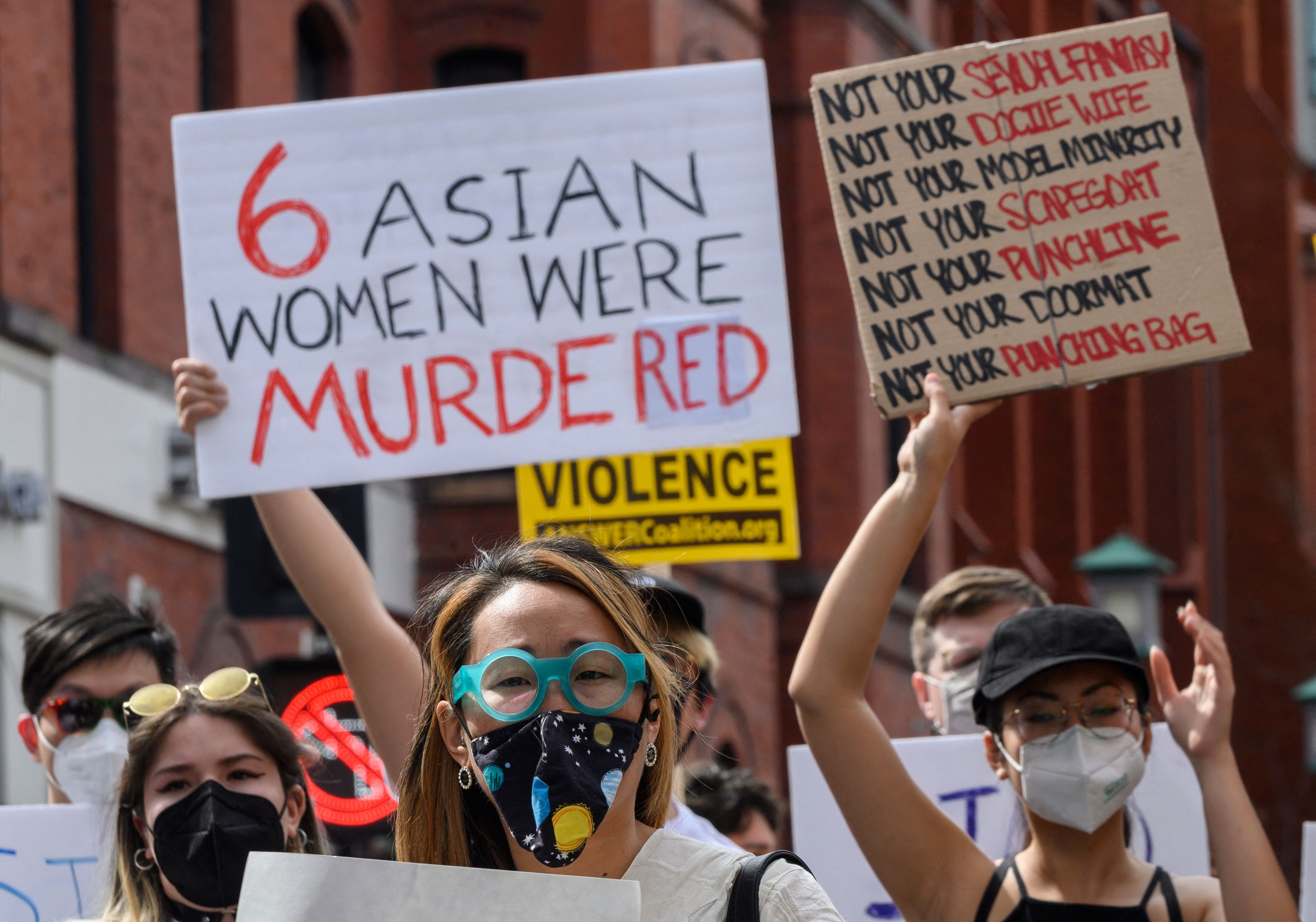 """Asian women at a protest in Washington's Chinatown on March 27, 2021. One woman is holding a sign that reads """"6 women were mu"""