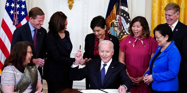 President Joe Biden hands out a pen after signing the COVID-19 Hate Crimes Act, in the East Room of the White House, Thursday, May 20, 2021, in Washington. Clockwise from left, Sen. Tammy Duckworth, R-Ill., Sen. Richard Blumenthal, D-Conn., Vice President Kamala Harris, Rep. Judy Chu, D-Calif., Rep. Grace Meng, D-N.Y., Rep. Don Beyer, D-Va., and Sen. Mazie Hirono, D-Hawaii. (AP Photo/Evan Vucci)