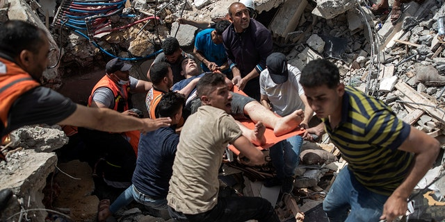 FILE - In this May 16, 2021, file photo, Palestinians rescue a survivor from the rubble of a destroyed residential building following deadly Israeli airstrikes in Gaza City. The Gaza Strip's already feeble health system is being brought to its knees by the fourth war in just over a decade. (AP Photo/Khalil Hamra, File)