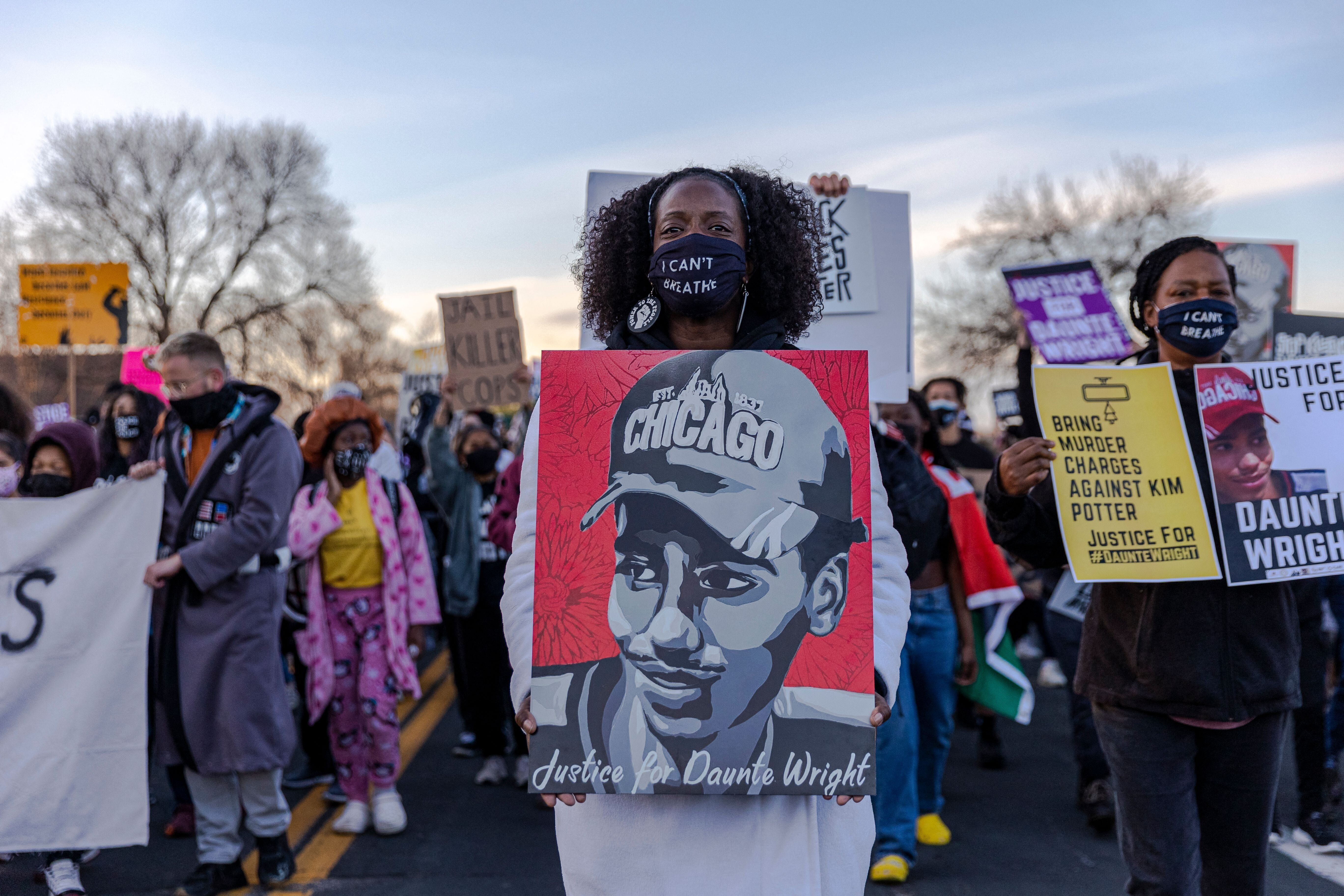 Demonstrators hold posters of Daunte Wright during a protest near the Brooklyn Center Police Department in Minnesota on April