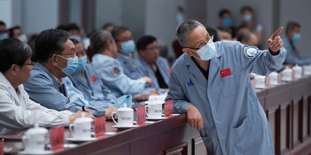 In this photo released by China's Xinhua News Agency, Zhang Rongqiao, right, the chief designer of China's Mars exploration mission, talks with Wu Weiren, second from left, the chief designer of China's lunar exploration project, at the Beijing Aerospace Control Center in Beijing, Saturday, May 22, 2021. China's first Mars rover has driven down from its landing platform and is now roaming the surface of the red planet, China's space administration said Saturday. (Jin Liwang/Xinhua via AP)