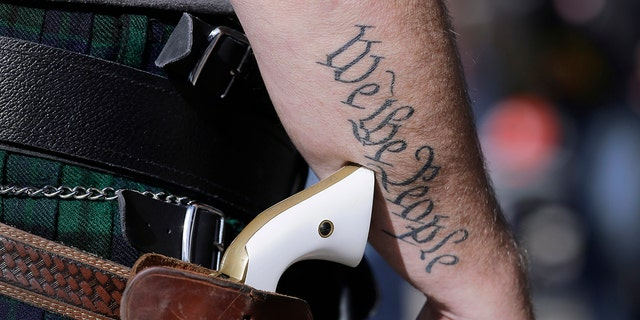 A supporter of open carry gun laws wears a pistol as he prepares for a rally in support of open carry gun laws at the Capitol, in Austin, Texas on Jan. 26, 2015. (AP Photo/Eric Gay, File)