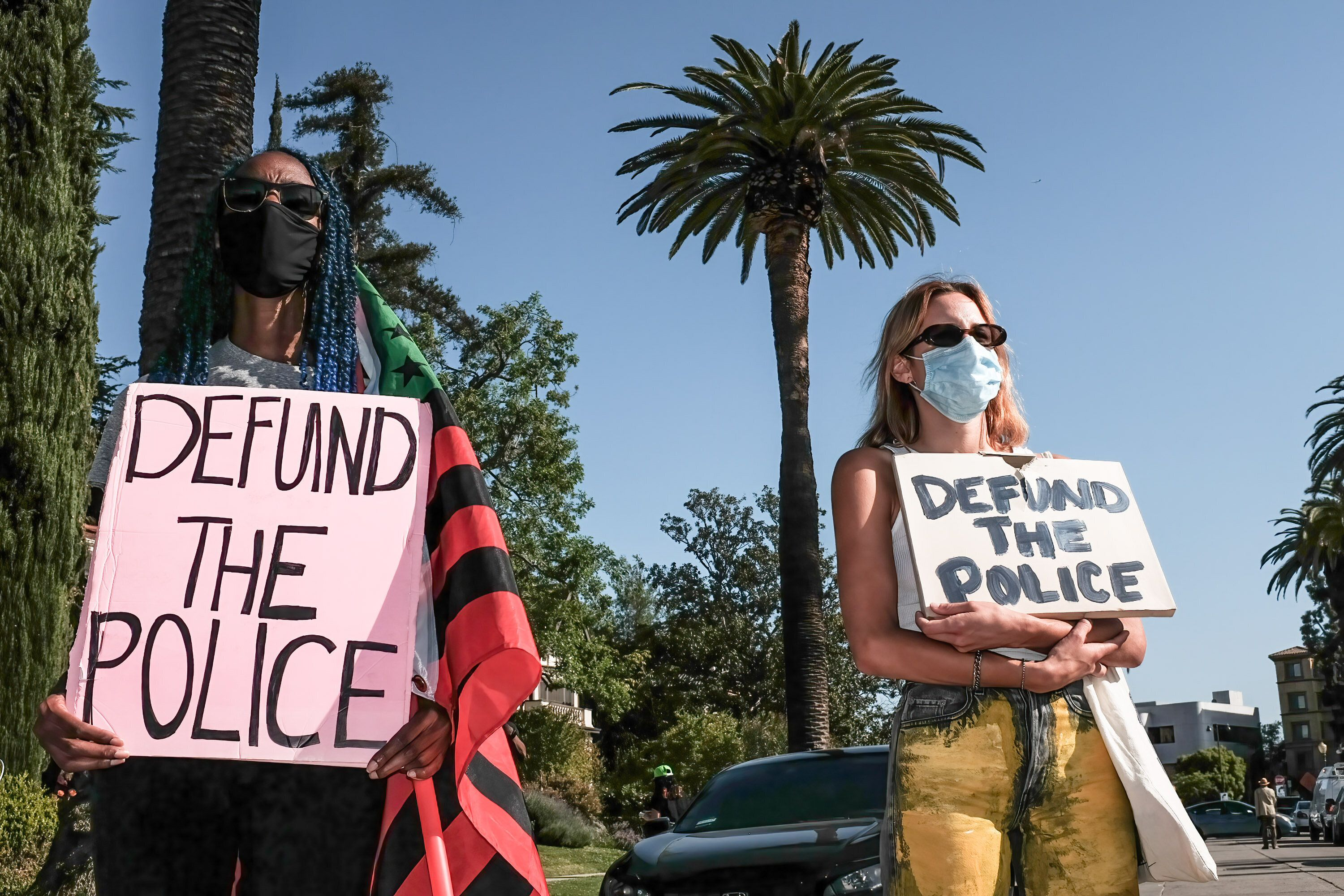 Protesters hold placards during a demonstration in April outside of Los Angeles Mayor Eric Garcetti's home to protest his pro