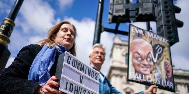 Protesters hold placards near Parliament Square, in London, on the day Dominic Cummings, the volatile advisor who until late last year was British Prime Minister Boris Johnson's most powerful and trusted aide, attended a select committee hearing at Portcullis House nearby, Wednesday, May 26, 2021. In recent days, Cummings has directed a torrent of criticism at Johnson's Conservative government in an ever-lengthening string of Twitter posts. On Wednesday, he plans to make the claims in person, testifying on live television to lawmakers investigating Britain's handling of COVID-19. (AP Photo/Alberto Pezzali)