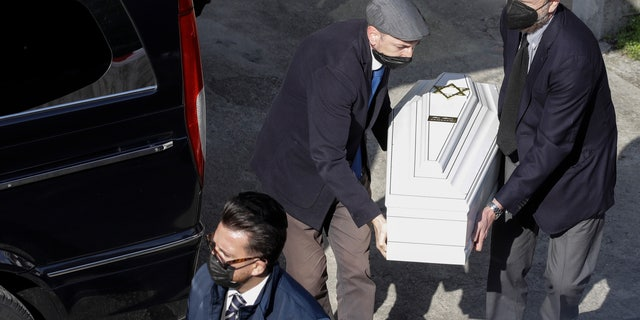 A white coffin is carried by members of the Jewish community at the morgue of Verbania Hospital, in Verbania, Italy, Wednesday, May 26, 2021. A prayer ceremony for the Jewish victims took place in Verbania Wednesday morning, before the bodies of the dead were released to return to their homes for funerals and burials. Three people were arrested following a cable car disaster that killed 14 people, after the lead cable apparently snapped and the cabin careened back down the mountain until it pulled off the line and crashed to the ground. (AP Photo/Luca Bruno)