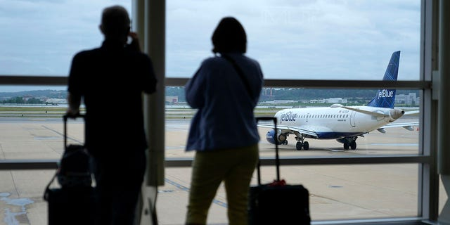 Travelers watch a JetBlue Airways aircraft taxi away from a gate at Ronald Reagan Washington National Airport ahead of Memorial Day weekend, Tuesday, May 25, 2021, in Arlington, Va. (AP Photo/Patrick Semansky)