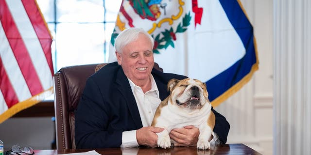 West Virginia Governor Jim Justice poses at his desk with his pet bulldog, Babydog, to urge COVID-19 vaccinations across the state. (Picture courtesy of the Office of Governor Jim Justice).