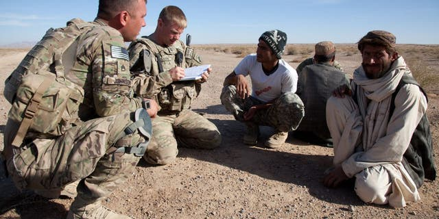 U.S. Army Staff Sgt. Nathaniel Johnson, U.S. Army Capt. James Nelson and Hader, interpreter, speak with elders in the Shorbak Desert, Kandahar Province, Afghanistan 9 Dec. 2011. (U.S. Army Photo by Spc. Phil Kernisan/Released)