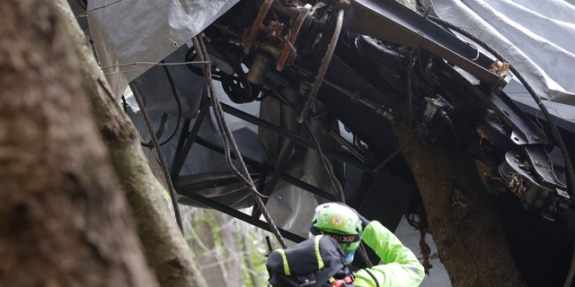 A rescuer takes a picture of a clamp that was placed on an emergency brake, as search for evidence continues in the wreckage of a cable car after it collapsed near the summit of the Stresa-Mottarone line in the Piedmont region, northern Italy, Wednesday, May 26, 2021. Police have made three arrests in the cable car disaster that killed 14 people after an investigation showed a clamp, placed on the brake as a patchwork repair effort, prevented the brake from engaging after the lead cable snapped. (AP Photo/Luca Bruno)