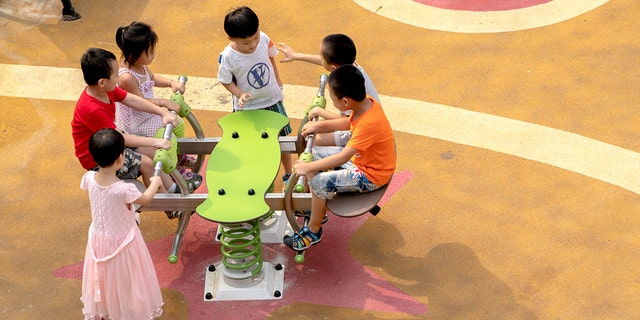 Kids are seen playing in a playground in a residential district. Though China tried to encourage young couple have more than one baby, the birth rate keeps decreasing in recent years. (Photo by Zhang Peng/LightRocket via Getty Images)