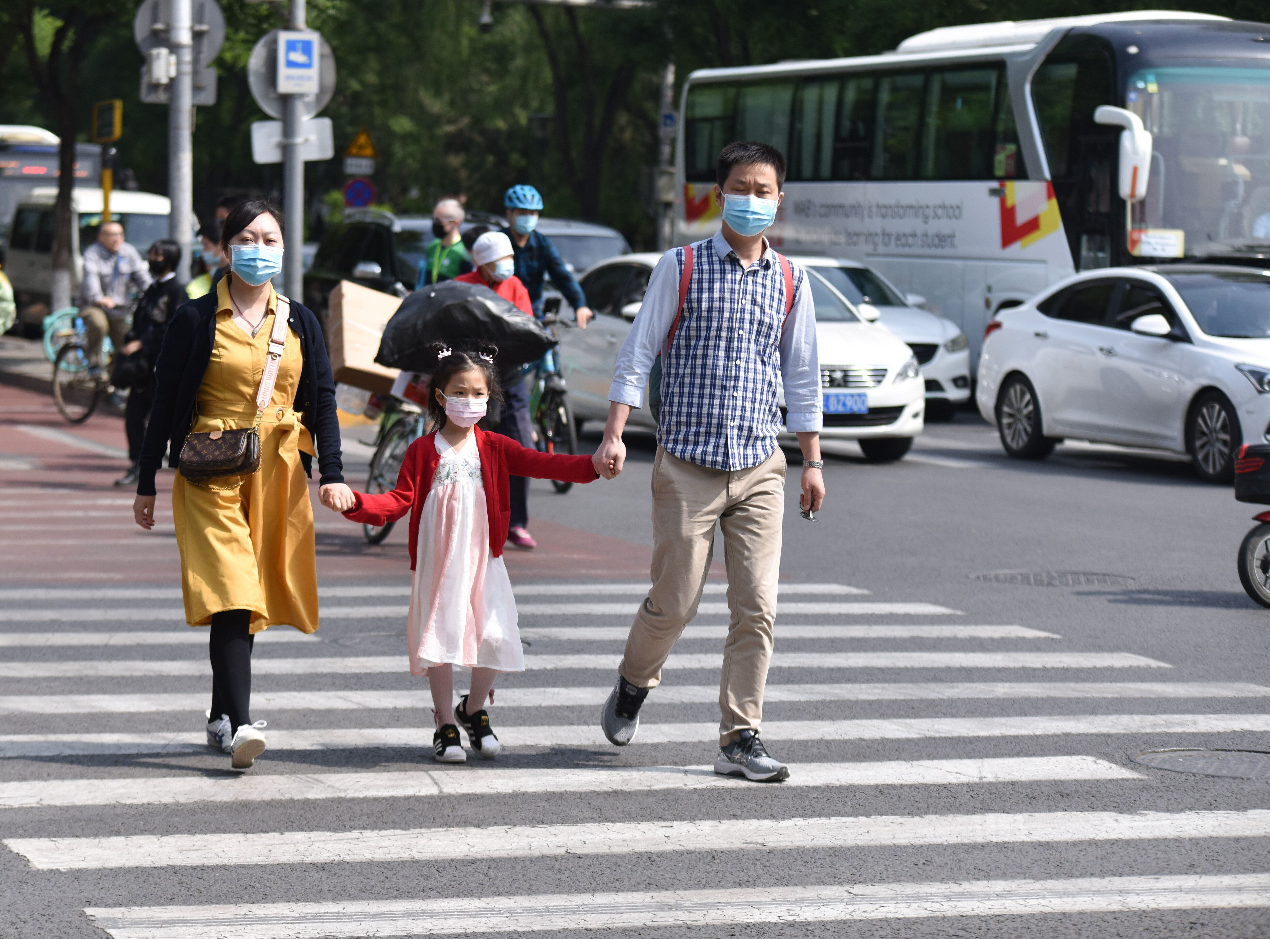 Parents with their kid walk along the Streets of Beijing. China's population has continued to grow since 2020, the National B