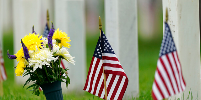 Flags and tributes mark the Memorial Day holiday are placed among the headstones in Fort Logan National Cemetery Monday, May 31, 2021, in southeast Denver. More than 105,000 graves were decorated with flags to mark the holiday.