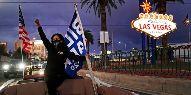 A Biden-Harris supporter carries flags while riding in the back of a limousine in Las Vegas, in this November 2020 file image. Nevada lawmakers have passed a bill aiming to make the state the first to weigh in on the 2024 presidential primary contests. (AP Photo/Jae C. Hong, File)