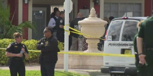 Florida authorities secure the scene at a Kissimmee, Fla., apartment complex where a Florida Department of Law Enforcement agent and a suspect exchanged gunfire Tuesday.