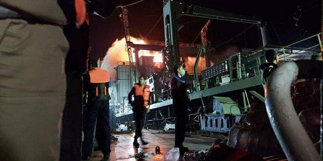 This photo made available by Asriran.com on Wednesday, June 2, 2021, shows personnel standing on Iran's navy support ship Kharg after being caught on fire in the Gulf of Oman. (Asriran.com via AP)