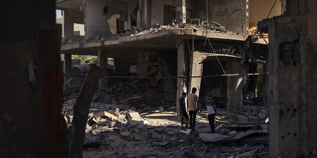 Palestinians stand among the rubble of a building that collapsed after it was hit by airstrikes during an 11-day war between Gaza's Hamas rulers and Israel, in Maghazi, Gaza Strip, Wednesday, June 2, 2021. (AP Photo/Felipe Dana)