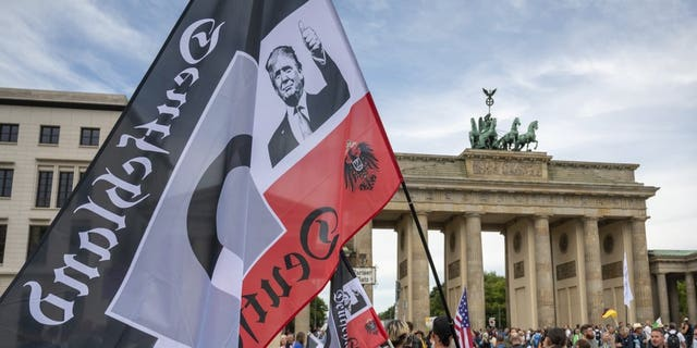 Protestors gather in front of the Brandenburg Gate before a demonstration against the coronavirus measures by the German Government in Berlin, Germany, Saturday, Aug. 29, 2020.