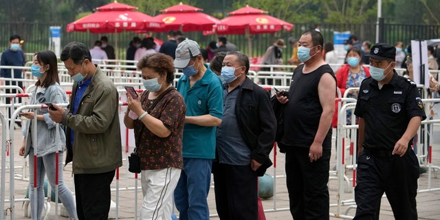 A security guard watches residents wearing face masks to help curb the spread of the coronavirus line up to receive the Sinopharm COVID-19 vaccine at a vaccination center in the Central Business District in Beijing, Wednesday, June 2, 2021. After a slow start, China is now doing what virtually no other country in the world can: harnessing the power and all-encompassing reach of its one-party system and a maturing domestic vaccine industry to administer shots at a staggering pace. (AP Photo/Andy Wong)