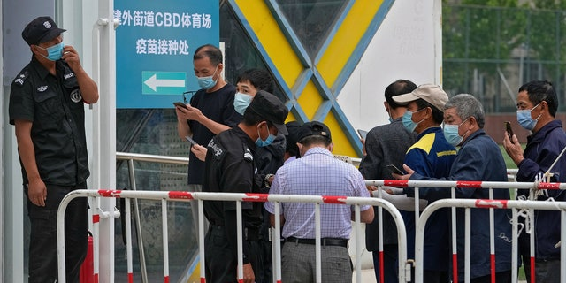 Security guards help masked residents to scan their health code as they line up to receive the Sinopharm COVID-19 vaccine at a vaccination center in the Central Business District in Beijing, Wednesday, June 2, 2021. After a slow start, China is now doing what virtually no other country in the world can: harnessing the power and all-encompassing reach of its one-party system and a maturing domestic vaccine industry to administer shots at a staggering pace. (AP Photo/Andy Wong)