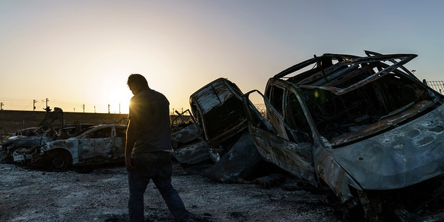 A worker passes torched cars piled up in a lot from clashes between Arabs, police, and Jews in the mixed Arab-Jewish town of Lod, central Israel, Tuesday, May 25, 2021. (AP Photo/David Goldman)