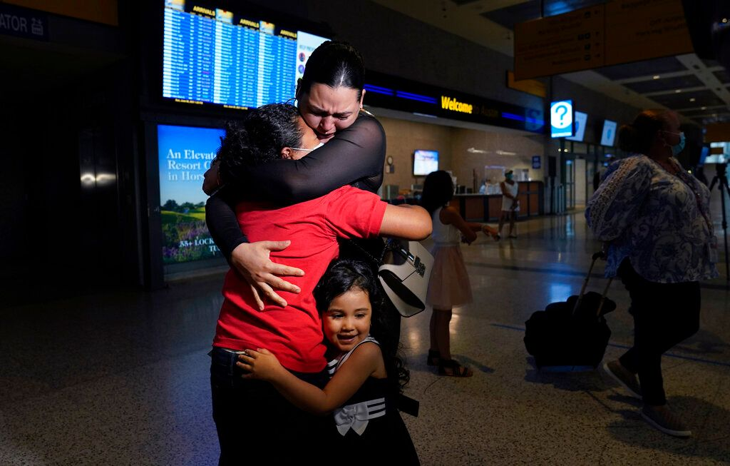 Emely, left, is reunited with her mother, Glenda Valdez and sister, Zuri, at Austin-Bergstrom International Airport, Sunday,