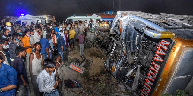 Onlookers gather near the wreckage after a bus carrying migrant workers after the lifting of coronavirus restrictions hit a delivery van on a highway near Kanpur, Uttar Pradesh state, India, Tuesday, June 8, 2021. (AP Photo)