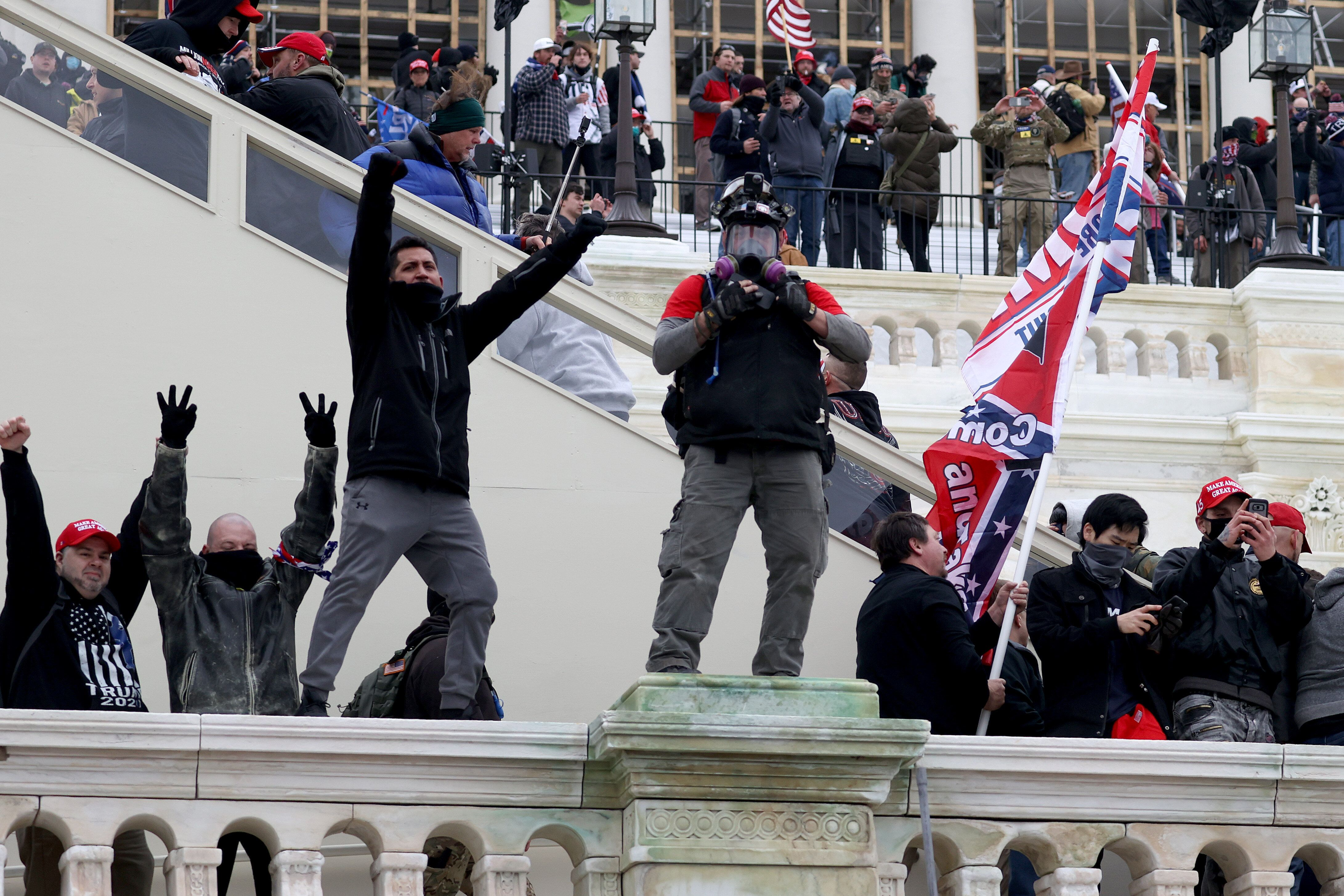 Russ Taylor (middle, in MAGA hat) on the west side of the Capitol during the attack. Another likely defendant, wearing a simi