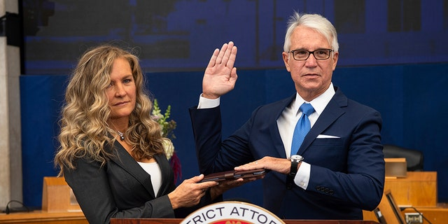 Incoming Los Angeles County District Attorney George Gascon is sworn in as his wife Fabiola Kramsky holds a copy of the Constitution during a mostly-virtual ceremony in downtown Los Angeles Monday, Dec. 7, 2020.