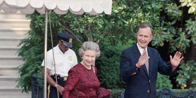 In this May 15, 1991, file photo, U.S. President George H.W. Bush escorts Queen Elizabeth II from the White House to a helicopter en route to Baltimore to watch her first major league baseball game, in Washington. (AP Photo/Doug Mills, File)