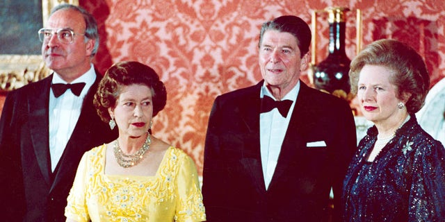 The June 10, 1984, file photo shows Queen Elizabeth II, second left, standing with West German Chancellor Helmut Kohl, left, U.S. President Ronald Reagan, second right, and Britain's Prime Minister Margaret Thatcher at London's Buckingham Palace, prior to a dinner for summit leaders. (AP Photo, File)