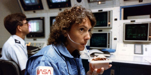 Christa McAuliffe, seen in 1985 taking a sip from a space-packaged drink prior to her ill-fated flight on space shuttle Challenger, was to teach from orbit. (NASA)