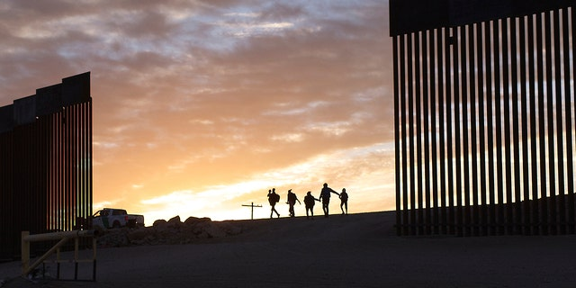 A pair of migrant families from Brazil pass through a gap in the border wall to reach the United States after crossing from Mexico in Yuma, Ariz., Thursday, June 10, 2021, to seek asylum. The families are part of an influx of asylum-seekers entering the U.S. in the Yuma area from South America and other continents. (AP Photo/Eugene Garcia)