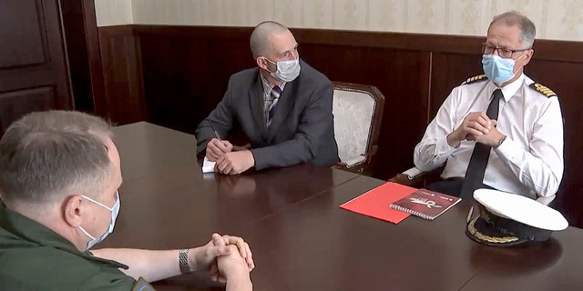 """In this photo taken from a video released by Russian Defense Ministry Press Service, Captain John Foreman, who is serving as the UK Defense Attaché in the British Embassy, right, attends a meeting in the Russian Defense Ministry in Moscow, Russia, Wednesday, June 23, 2021. The Defense Ministry said it called in the U.K. military attache in Moscow to protest the destroyer's """"dangerous move"""" and urged British authorities to investigate the crew's actions. (Russian Defense Ministry Press Service via AP)"""
