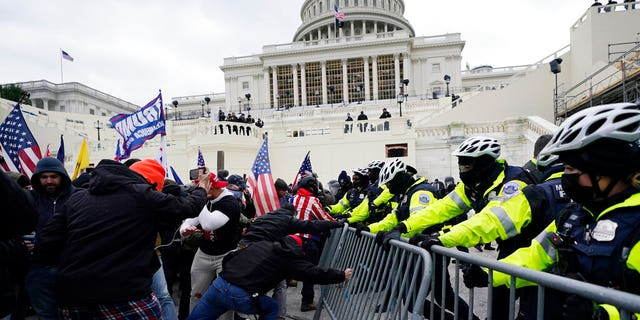 Trump supporters try to break through a police barrier, Wednesday, Jan. 6, 2021, at the Capitol in Washington, D.C. (AP Photo/Julio Cortez)