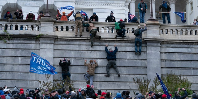 Supporters of President Trump climb the west wall of the U.S. Capitol on Wednesday, Jan. 6, 2021, in Washington, D.C.
