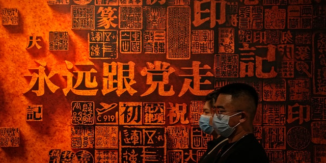 """A couple wearing face masks to help curb the spread of the coronavirus walk by a display board with the words """"Always follow the party"""" on display an exhibition promoting China's achievement under the communist party from 1921 to 2021, in Beijing, Sunday, June 20, 2021. (AP Photo/Andy Wong)"""