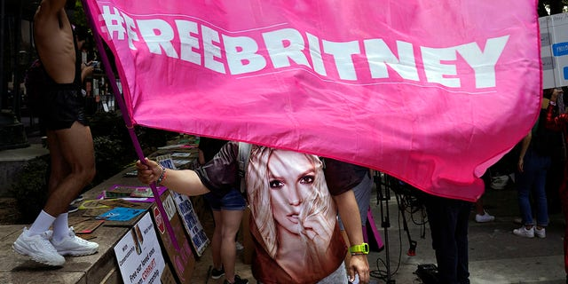 """A Britney Spears supporter waves a """"Free Britney"""" flag outside a court hearing concerning the pop singer's conservatorship at the Stanley Mosk Courthouse, Wednesday, June 23, 2021, in Los Angeles."""