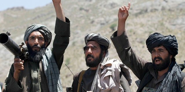 Taliban fighters react to a speech by their senior leader in the Shindand district of Herat province, Afghanistan, in 2016.