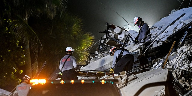EDITORS NOTE: Graphic content / Search and Rescue personnel hold a stretcher after recovering a body out of the rubble after the partial collapse of the Champlain Towers South in Surfside, north of Miami Beach, on June 24, 2021. (Photo by CHANDAN KHANNA/AFP via Getty Images)