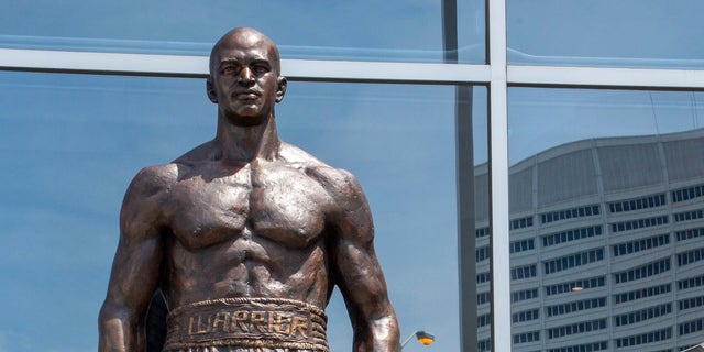Legendary boxer Evander Holyfield stands next to a bronze statue of himself that was unveiled outside the State Farm Arena, Friday, June 25, 2021, in Atlanta. (Associated Press)